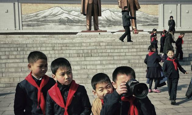 In this Feb. 16, 2013 photo taken with an iPhone and posted to Instagram on Feb. 16 , 2013, North Korean school boys play with an Associated Press photographer's professional camera in front of statues of the late leaders Kim Il Sung and Kim Jong Il, on Mansu Hill in Pyongyang, North Korea. On Jan. 18, 2013, foreigners were allowed for the first time to bring mobile phones into North Korea. And this week the local service provider, Koryolink, is allowing foreigners to access the Internet on a data capable 3G connection on mobile phones.(AP Photo/David Guttenfelder)