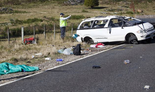 Policemen examine the scene of a minivan crash near Turangi, New Zealand, Saturday, May 12, 2012. Three Boston University students who were studying in New Zealand were killed Saturday when their minivan crashed. At least five other students from the university were injured in the accident, including one who was in critical condition. (AP Photo/New Zealand Herald, John Cowpland) NEW ZEALAND OUT, AUSTRALIA OUT