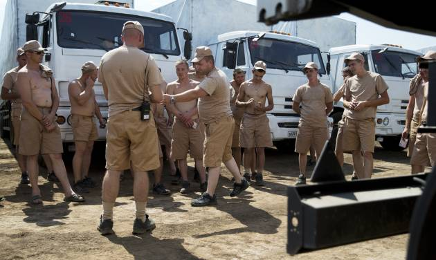 Drivers listen to instructions as they stand near their  white trucks with humanitarian aid after parking in a field about 28 kilometers from Ukrainian border in Rostov-on-Don region, Russia, Thursday, Aug. 14, 2014. Russia on Tuesday dispatched some hundreds of trucks, although only a small proportion were counted in this convoy, covered in white tarps on a mission to deliver aid to a rebel-held zone in eastern Ukraine. (AP Photo/Pavel Golovkin)