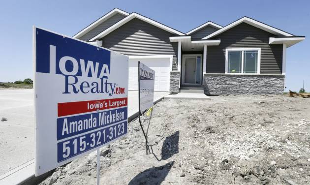 In this May 21, 2014 photo, a sign sits in front of a new home for sale in West Des Moines, Iowa.  The Commerce Department reports on sales of new homes in April on Friday, May 23, 2014. (AP Photo/Charlie Neibergall)