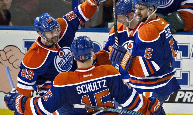 Edmonton Oilers' Sam Gagner (89), Nick Schultz (15), Ales Hemsky (83) and Mark Fraser (5) celebrate a goal against the Ottawa Senators during the second period of an NHL hockey game, Tuesday, March 4, 2014 in Edmonton, Alberta. (AP Photo/The Canadian Press, Jason Franson)