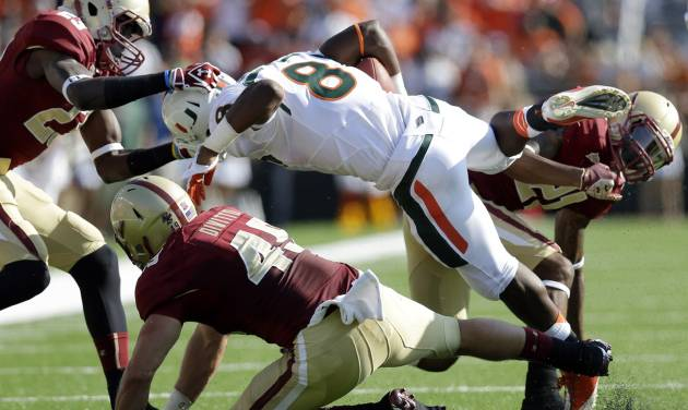 Miami running back Duke Johnson (8) carries the ball against Boston College defensive back Jim Noel (23), linebacker Steele Divitto (49), and defensive back Manuel Asprilla (21) in the first half of an NCAA college football game at Alumni Stadium in Newton, Mass. Saturday, Sept. 1, 2012. Miami won 41-32. (AP Photo/Elise Amendola)