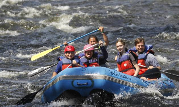FILE - This Aug. 5, 2011 file photo shows whitewater rafters going down the Sacandaga River in Lake Luzerne, N.Y.  Activities like whitewater rafting, ziplining, surfing and stand-up paddleboarding often appeal to teenagers, even when they're at the age where they're not all that excited about vacationing with their parents. Being flexible about itineraries, letting teens help plan outings and including activities that they'll enjoy can make traveling with teens more fun for everyone. (AP Photo/Mike Groll, File)