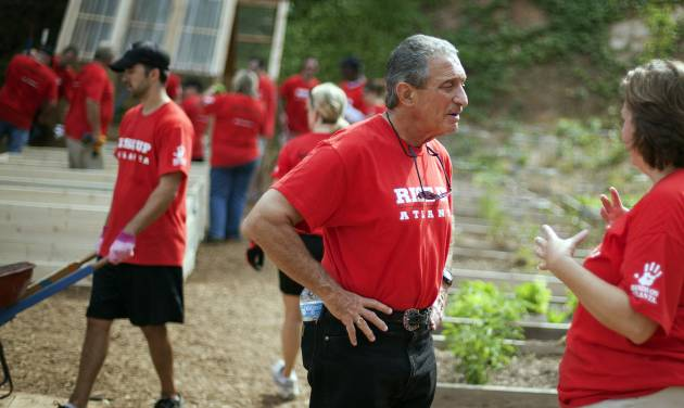 Atlanta Falcons owner Arthur Blank, center, talks with Falcons director of human resources Karen Walters during a day of volunteering at the non-profit organization City of Refuge, Thursday, May 3, 2012, in Atlanta. Blank has paired his team with Hands On Atlanta, a community-based volunteer organization, in encouraging fans to give their time and energy to improve life in Atlanta. Blank and about 180 representatives of the Falcons and other of his businesses gathered to work on four key projects: constructing an indoor playground, planting an urban garden, remodeling resident dormitories, and painting an indoor mural. (AP Photo/David Goldman)