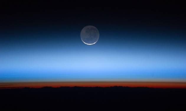 This undated image made available by NASA and photographed by the Expedition 28 crew aboard the International Space Station, shows the moon, at center with the limb of Earth near the bottom transitioning into the orange-colored troposphere, the lowest and most dense portion of the Earth's atmosphere.  A team of former NASA executives are launching a private venture to send people to the moon for $1.5 billion. The newly formed business is offering countries a two-person trip to the moon, either for research or national prestige. The venture was announced Wednesday, Dec. 6, 2012. (AP Photo/NASA)