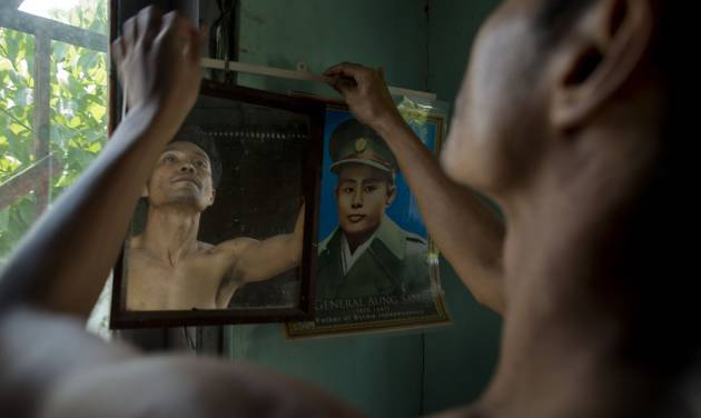 In this March 25, 2013 photo, San Zaw Htwe adjusts a portrait of Independence hero Gen. Aung San in his room in Yangon, Myanmar. The former political prisoner will turn 39 on Saturday, March 30, the second anniversary of the day President Thein Sein took office and pledged to transform Myanmar from a military dictatorship to a free-market democracy. Thein Sein's administration has made remarkable progress toward that goal, but at a price that San Zaw Htwe knows only too well: forgetting the past. (AP Photo/Gemunu Amarasinghe)