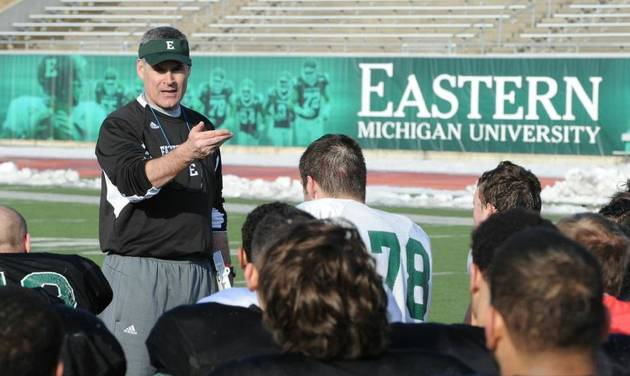 In an undated photo provided by Eastern Michigan University, head football coach Chris Creighton talks to his team in Ypsilanti, Mich. The new football coach wants his team to have the attitude that it will play anyone, anywhere. Creighton says the Eagles are so tough they would play on a parking lot. (AP Photo/Eastern Michigan University, HOPD)