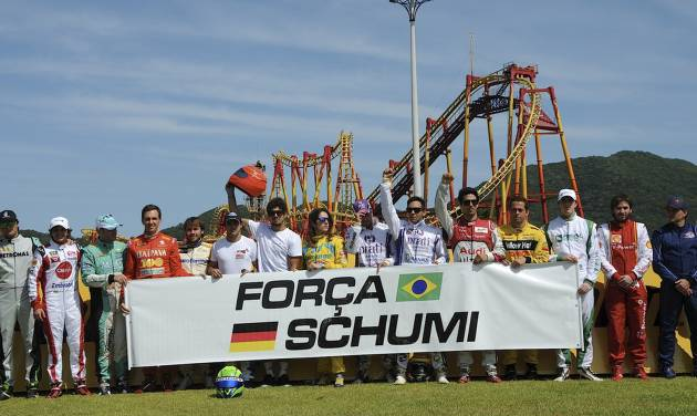 "In this photo released by Desafio Internacional das Estrelas, pilots taking part in the karting race International Challenge of the Stars hold a banner that reads in Portuguese ""Strength Schumi,"" a message for Michael Schumacher, in Penha, Brazil, Saturday, Jan. 11, 2014. Schumacher, who won the annual karting event in 2007 and 2009, has been in a medically induced coma since Dec. 29, 2013 when he struck his head on a rock while skiing on a family vacation. (AP Photo/Duda Bairros, Desafio Internacional das Estrelas)"