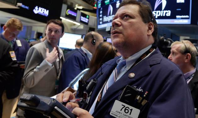 Trader John Santiago, right, works on the floor of the New York Stock Exchange Friday, May 30, 2014. Two negative reports on U.S. consumers were pushing stocks lower in early trading Friday. (AP Photo/Richard Drew)