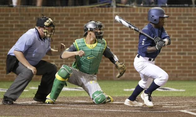 Vanderbilt's Ro Coleman hits a pinch-hit single with the bases loaded in the bottom of the ninth inning to drive in the winning run and give Vanderbilt a 3-2 win over Oregon in an NCAA college baseball regional tournament game Sunday, June 1, 2014, in Nashville, Tenn. Catching for Oregon is Jack Kruger. (AP Photo/Mark Humphrey)