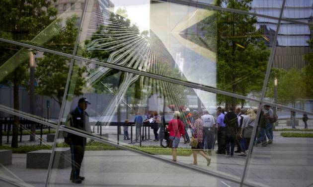 FILE - With an image of the former World Trade Center seen through the reflective windows of the 9/11 Memorial Museum, some of the first public visitors can be seen arriving at the site in New York in this Wednesday, May 21, 2014 file photo. Organizers say over 300,000 people have visited the Sept. 11 museum since it opened little more than a month ago, and that has exceeded their expectations. (AP Photo/Craig Ruttle, File)