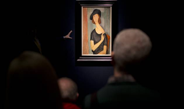 """The gesturing hand of an expert speaking to a group of people is lit by a spotlight illuminating the painting entitled """"Jeanne Hebuterne (Au chapeau)"""" by Italian artist Amedeo Modigliani at Christie's auction house in London, Friday, Feb. 1, 2013. The piece is estimated to fetch between 16 and 22 million pounds ($25.3 to $34.8 million or 18.5 to 25.5 million euro) in the forthcoming Impressionist and Modern Art evening sale in London on February 6.  (AP Photo/Matt Dunham)"""