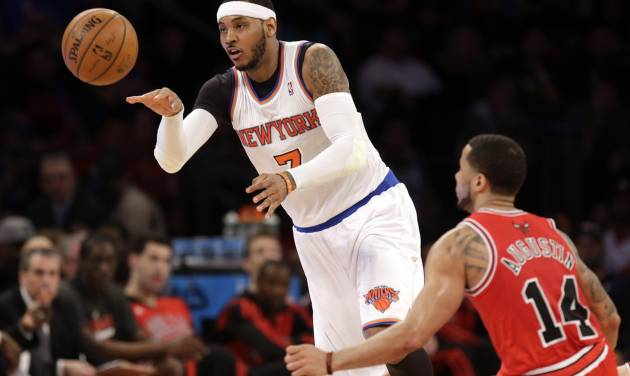 New York Knicks' Carmelo Anthony, left, passes the ball past Chicago Bulls' D.J. Augustin during the first half of the NBA basketball game, Sunday, April 13, 2014 in New York. The Knicks defeated the Bulls 100-89. (AP Photo/Seth Wenig)