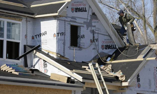 FILE - In this Dec. 27, 2013 file photo, a builder works on the the roof of a new home under construction in Wilmette, Ill. The National Association of Home Builders reports on sentiment among U.S. builders on Monday, March 17, 2014. (AP Photo/Nam Y. Huh, File)