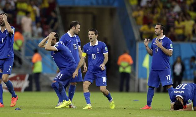 Greek players react during a penalty shootout at the end of the World Cup round of 16 soccer match between Costa Rica and Greece at the Arena Pernambuco in Recife, Brazil, Sunday, June 29, 2014. Costa Rica won 5-3 on penalties after the match ended 1-1. (AP Photo/Andrew Medichini)