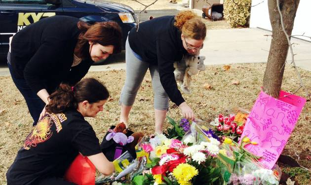 CORRECTS LAST NAME OF VICTIM'S MOTHER TO BARFIELD INSTEAD OF OWENS - Stacey Barfield, mother of Hailey Owens, kneeling, and family members Sara Wells, left, and Teri Nord arrange flowers left by well wishers Thursday, Feb. 20, 2014 near the site where the 10-year-old girl was abducted just blocks from the Springfield, Mo., home. Prosecutors have charged Craig Michael Wood with first-degree murder, kidnapping and armed criminal action in their girls death. Prosecutors says the fourth-grader's body was found stuffed in two trash bags inside plastic storage containers in the basement of Wood's Springfield home. She had been shot in the head. (AP Photo/Alan Scher Zagier)