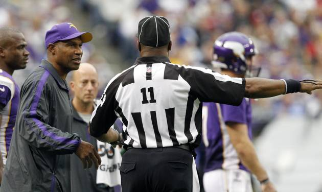 Minnesota Vikings head coach Leslie Frazier, left, talks with side judge Dwayne Strozier, right, during the second half of an NFL football game against the San Francisco 49ers Sunday, Sept. 23, 2012, in Minneapolis. The Vikings won 24-13. (AP Photo/Genevieve Ross)