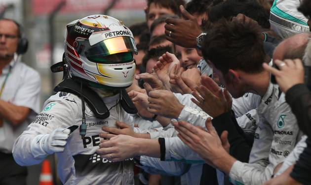 Mercedes driver Lewis Hamilton of Britain, left, is congratulated by his team members after the Chinese Formula One Grand Prix at Shanghai International Circuit in Shanghai, Sunday, April 20, 2014. (AP Photo/Eugene Hoshiko)