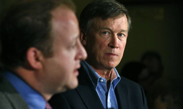 Colo. Gov. John Hickenlooper, right, listens as U.S. Rep. Jared Polis, D-Colo., takes questions during a news conference about fracking, at the Capitol, in Denver, Monday Aug. 4, 2014. Polis joined Hickenlooper on Monday Aug. 4 to detail what they're pitching as a compromise to prevent four initiatives that support or oppose fracking.  (AP Photo/Brennan Linsley)