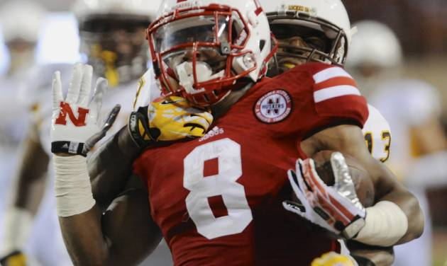 Wyoming linebacker Devyn Harris, rear, tackles Nebraska running back Ameer Abdullah (8), in the first half of an NCAA college football game in Lincoln, Neb., Saturday, Aug. 31, 2013. (AP Photo/Dave Weaver)
