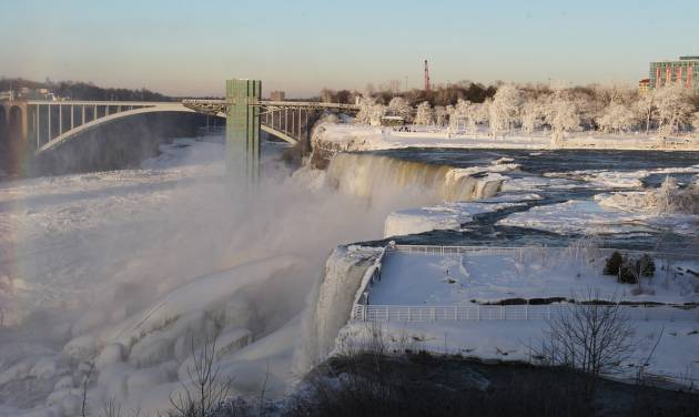 The area surrounding Niagara Falls is coated in a layer of ice in Niagara Falls State Park, Niagara Falls, N.Y. on Thursday, Jan. 9, 2014.  Niagara Falls hasn't frozen over, but it has become an icy spectacle, thanks to a blast of arctic wind and cold that blew around and froze the mist on surfaces and landscaping. Despite the urban legends, Niagara Falls doesn't freeze solid in the winter, tourism officials say.  A section of the American Falls, one of three waterfalls that make up the natural attraction, has frozen. The Niagara River rapids and larger Horseshoe Falls continue to flow unimpeded. (AP Photo/The Buffalo News, Sharon Cantillon)  MANDATORY CREDIT
