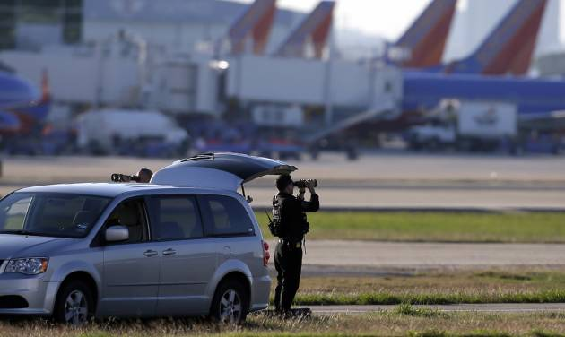 A member of the security detail keeps watch on the tarmac while awaiting the arrival of President Barack Obama at Love Field Airport, Wednesday, Nov. 6, 2013, in Dallas. (AP Photo/Tony Gutierrez)