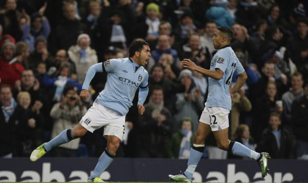 Manchester City's Carlos Tevez, left, celebrates with teammate Gael Clichy after scoring against Swansea during their English Premier League soccer match at The Etihad Stadium, Manchester, England, Saturday, Oct. 27, 2012. (AP Photo/Jon Super)