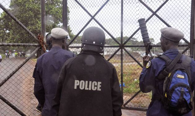 Liberian Police dressed in riot gear deploy at a MSF, 'Doctors Without Borders', Ebola treatment center, in the rain, as they provide security in the city of Monrovia, Liberia, Monday, Aug. 18, 2014. Liberia's armed forces were given orders to shoot people trying to illegally cross the border from neighboring Sierra Leone, which was closed to stem the spread of Ebola, local newspaper Daily Observer reported Monday. (AP Photo/Abbas Dulleh)
