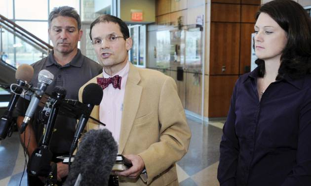 Defense attorney Jim Fleming, center, is flanked by Todd Hoffner, left, and his wife Melodee Hoffner as he makes a statement, Wednesday, Oct. 31, 2012, following Todd Hoffner's court testimony in Mankato, Minn., on child pornography charges. Hoffner, the suspended head football coach at Minnesota State, Mankato who is accused of making pornographic videos of his children, told a judge Wednesday that the images merely show a skit that his children came up while in the bathtub and asked him to record. (AP Photo/The Mankato Free Press, John Cross)