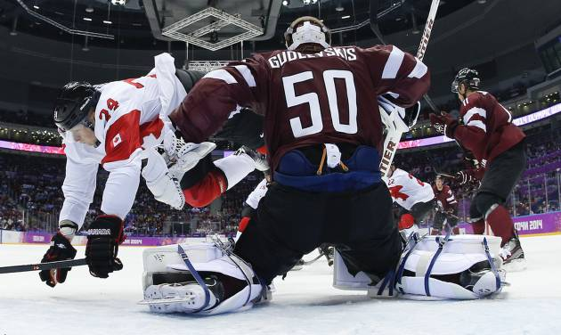 Canada forward Corey Perry trips over Latvia goaltender Kristers Gudlevskis in the first period of a men's ice hockey game at the 2014 Winter Olympics, Wednesday, Feb. 19, 2014, in Sochi, Russia. (AP Photo/Julio Cortez, Pool)