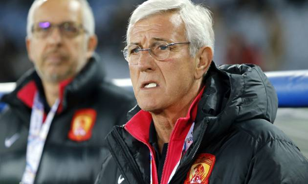 """FILE - In this March 12, 2014 file photo, Guangzhou Evergrande coach Marcello Lippi, right, waits for the start of his team's match against Yokohama F. Marinos during their group stage soccer match of the AFC Champions League in Yokohama, near Tokyo. Italian coach Marcello Lippi has been provisionally suspended for one match for confronting a referee during his Chinese club Guangzhou Evergrande's 1-0 loss in Sydney to the Western Sydney Wanderers in the Asian Champions League quarterfinals. The Asian Football Confederation announced the provisional ban Sunday, Aug. 24, 2014, saying the final decision of its disciplinary committee """"will be issued following the completion of a full investigation."""" (AP Photo/Shuji Kajiyama, File)"""