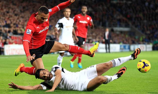 Swansea City's Andrew Taylor (right) and Cardiff City's Peter Odemwingie battle for the ball during the English Premier League match at the Cardiff City Stadium, Sunday Nov. 3, 2013. (AP Photo / Nick Potts/PA) UNITED KINGDOM OUT  NO SALES  NO ARCHIVE
