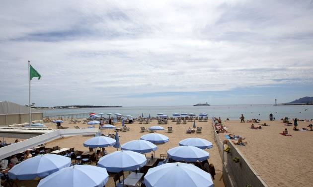 This May 12, 2014 photo shows people on the beach of Cannes, France. Cannes is a favorite destination for the wealthy _ and for celebrities who walk the red carpet at the Cannes Film Festival each May _ but the Riviera resort also offers plenty of simple, inexpensive pleasures, from the beach to street strolls. (AP Photo/Virginia Mayo)