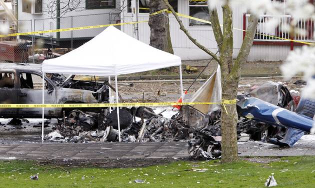 Caution tape surrounds the charred wreckage of a news helicopter and two vehicles after the chopper crashed into a city street near the Space Needle, Tuesday, March 18, 2014, in Seattle. Two people were killed and another critically injured. (AP Photo/Stephen Brashear)