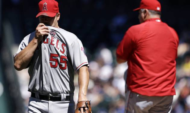 Los Angeles Angels starting pitcher Joe Blanton, left, heads off the field after being relieved in the fifth inning of a baseball game against the Seattle Mariners, Sunday, July 14, 2013, in Seattle. (AP Photo/Elaine Thompson)