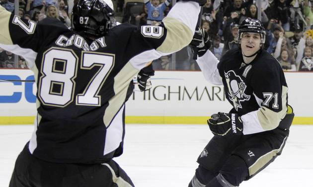 Pittsburgh Penguins' Evgeni Malkin (71) celebrates his 50th goal of the season with teammate Sidney Crosby in the second period of an NHL hockey game against the Philadelphia Flyers in Pittsburgh Saturday, April 7, 2012. (AP Photo/Gene J. Puskar)