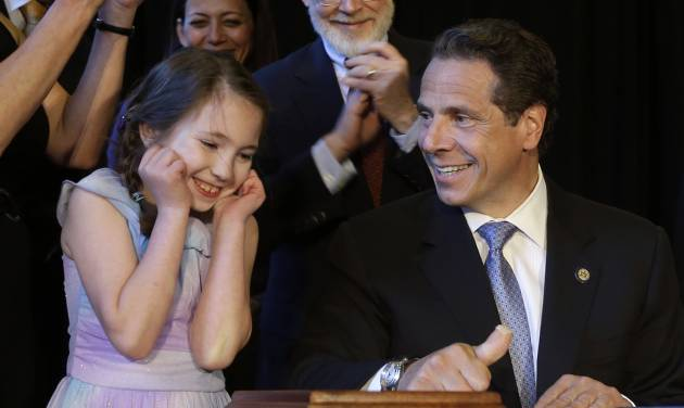 New York Governor Andrew Cuomo, right, gets some help from Amanda Houser, 10, while signing a ceremonial bill to establish a medical marijuana program in New York, Monday, July 7, 2014. New York has become the 23rd state in the U.S. to authorize medical marijuana,  though the state's program is one of the nation's most restrictive.  Cuomo signed the measure into law on Saturday and held the formal signing ceremony on Monday to highlight the new law.  When the program gets up and running in about 18 months, patients with diseases including AIDS, cancer and epilepsy will be able to obtain non-smokeable versions of the drug. Instead, the drug must be ingested or administered through a vaporizer or oil base. Houser, who has Dravet syndrome, may benefit from medical marijuana.(AP Photo/Seth Wenig)