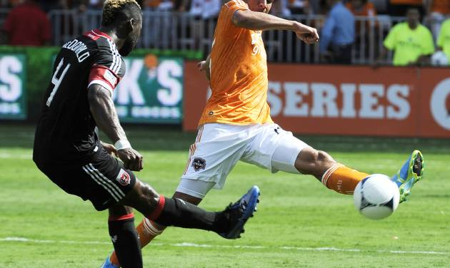 Houston Dynamo's Brian Ching, right, tries to get the ball past D.C. United's Brandon McDonald (4) in the first half of an MLS soccer match, Saturday, May 12, 2012, in Houston. (AP Photo/Pat Sullivan)