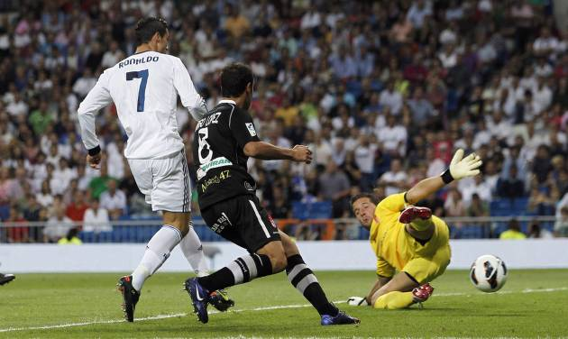 Real Madrid's Cristiano Ronaldo from Portugal, left, scores his second goal during a Spanish La Liga soccer match against Granada at the Santiago Bernabeu stadium in Madrid, Spain, Sunday, Sept. 2, 2012. (AP Photo/Andres Kudacki)