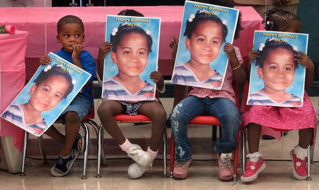 FILE - In this Thursday, Sept. 29, 2005, file photo, children hold posters of missing child, Rilya Wilson, at the Caleb Center in Miami, during a birthday party thrown by community leaders from Rilya's old neighborhood to remember what would have been her ninth birthday. More than a decade after foster child Rilya Wilson's disappearance caused a state government shakeup, trial is finally scheduled to begin for the caregiver accused of killing the little girl. Jury selection is scheduled to begin Monday, Nov. 5, 2012, for the trial of Geralyn Graham, who has pleaded not guilty to a first-degree murder charge and has insisted she is innocent.(AP Photo/Miami Herald, Marice Cohn Band)