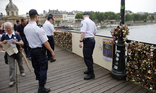 French police officers check out a wooden repaired section of the Pont des Arts bridge after a chunk of fencing with thousands of locks fell off under their weight in Paris, Monday, June 9, 2014. The thousands of locks that cling like barnacles to the Pont des Arts in Paris have become a symbol of danger, rather than love, after a chunk of fencing fell off under their weight. The fencing tumbled late Sunday on the pedestrian bridge, which crosses the Seine. (AP Photo/Francois Mori)
