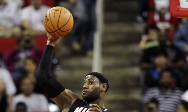 Miami Heat's LeBron James (6) saves the ball from going out of bounds as Charlotte Bobcats' DaJuan Summers and Bismack Biyombo (0) watch during the first half of an NBA preseason basketball game in Raleigh, N.C., Tuesday, Oct. 23, 2012. (AP Photo/Gerry Broome)