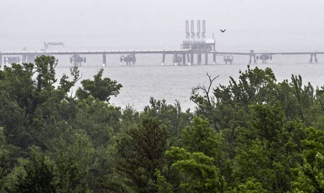 This photo taken June 12, 2014 shows a half-a-mile long, the Dominion Energy's Cove Point LNG Terminal's offshore loading platform, a mile offshore seen from the facilities nature preserve which surround the plant in Lusby, Md. Richmond, Virginia-based Dominion wants to build the $3.8 billion project at its existing Cove Point liquefied natural gas terminal on the bay, which the company used for years to import natural gas. Now, thanks to a boom in natural gas fueled by hydraulic fracturing, Dominion has contracts to export natural gas to Japan and India, where gas prices are higher than in the U.S.  (AP Photo/Cliff Owen)