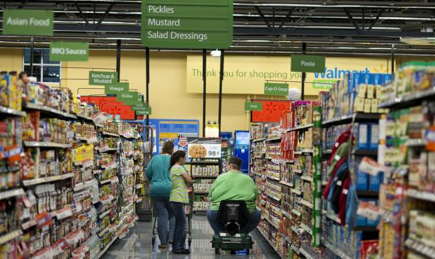 Customers shop at Wal-Mart Neighborhood Market in Bentonville, Ark., Thursday, June 5, 2014. Wal-Mart's supercenters still account for 80 percent of its 4,000-plus U.S. stores, but the retailer is opening smaller outlets that cater to shoppers looking for more convenience. It now plans to open 270 to 300 small stores during the current fiscal year — double its initial forecast. (AP Photo/Sarah Bentham)
