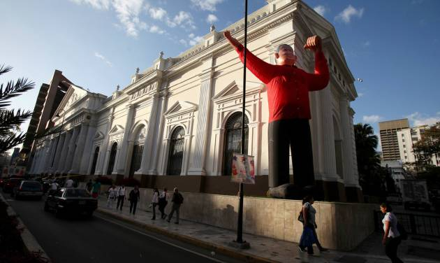 An inflatable doll depicting Venezuela's President Hugo Chavez sits in front of Venezuela's National Assembly in Caracas, Venezuela, Monday, Feb. 18, 2013. Chavez returned to Venezuela early Monday after more than two months of medical treatment in Cuba following cancer surgery, and was being treated at the Caracas' military hospital, his government said. (AP Photo/Fernando Llano)