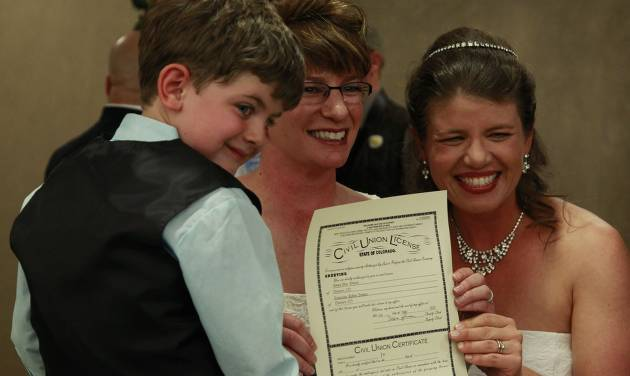 Just after midnight, Fran Simon, left, and her partner Anna Simon, flanked by their son Jeremy, age 5, display their State of Colorado civil union license shortly before making their vows during a ceremony at the Webb Municipal Building in Denver, Wednesday May 1, 2013. Fran Simon, left, and her partner Anna Simon were the first couple to receive a certificate. In March 2013, the Colorado General Assembly passed SB-11, the Colorado Civil Union Act, which provides committed same-sex couples with legal protections and responsibilities. The act went into effect on May 1, 2013. (AP Photo/Brennan Linsley)