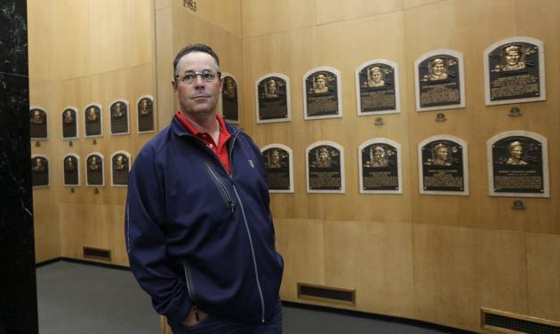 Former Atlanta Braves pitcher Greg Maddux walks through the Plaque Gallery during his orientation visit at the Baseball Hall of Fame on Monday, March 24, 2014, in Cooperstown, N.Y. Maddux will be inducted to the hall in July. (AP Photo/Mike Groll)