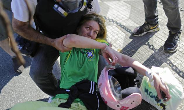 A press photographer helps a Brazil soccer fan affected by tear gas when she got caught up in clashes between police and protesters while trying to reach the stadium for the opening World Cup soccer game in Sao Paulo, Brazil, Thursday, June 12, 2014.  Brazilian police clashed with anti-World Cup protesters trying to block part of the main highway leading to the stadium that was hosting the opening match between Brazil and Croatia. (AP Photo/Nelson Antoine)