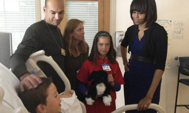 In this photo provided by the Hern family, first lady Michelle Obama, right, visits with  Aaron Hern, lower left, his parents Alan and Katherine, and sister Abby, all of Martinez, Calif., at Massachusetts General Hospital in Boston Thursday, April 18, 2013. Aaron Hern, 11, was among those injured by one of the bomb blasts near the Boston Marathon finish line Monday.  (AP Photo/Hern Family)