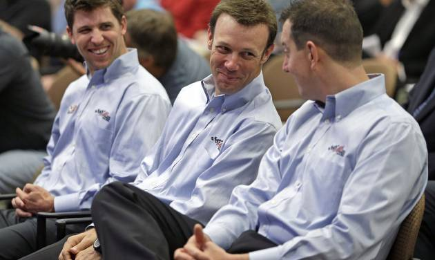 Drivers, from left, Denny Hamlin, Matt Kenseth, and Kyle Busch, share a laugh during a news conference at Joe Gibbs Racing's headquarters in Huntersville, N.C., Tuesday, Aug. 19, 2014. Joe Gibbs Racing has hired Carl Edwards to drive a new fourth Sprint Cup car in 2015 and Daniel Suarez will drive in the Nationwide series. (AP Photo/Chuck Burton)